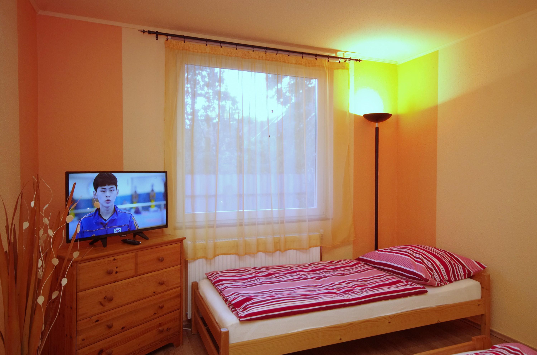 Egyszemélyes ágy és LED TV az őszi szobában a gyulai Bodza apartmanban