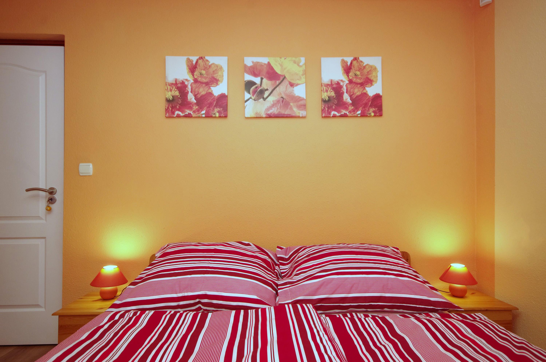 Kétszemélyes franciaágy és éjjeliszekrények az őszi szobában a gyulai Bodza apartmanban
