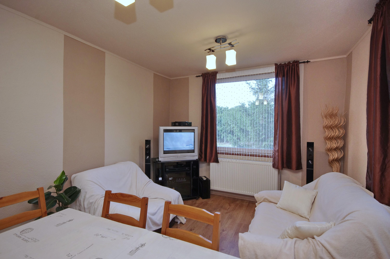 Nappali szoba kanappéval, karosszékkel, TV-sarokkal a gyulai Bodza apartmanban