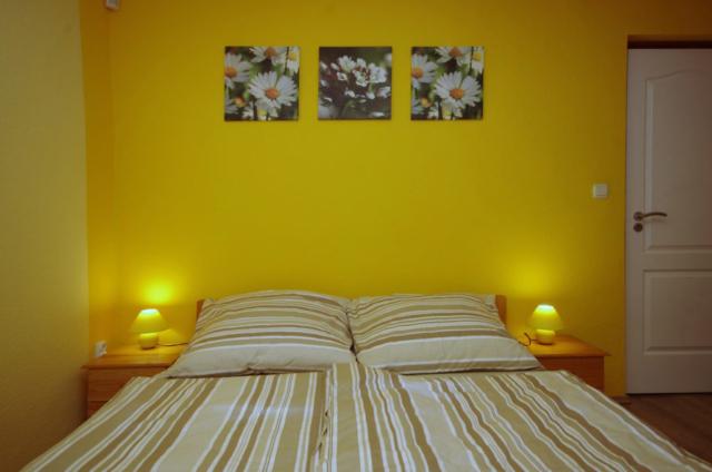 Kétszemélyes francia ágy és éjjeli szekrények a nyári szobában a gyulai Bodza apartmanban