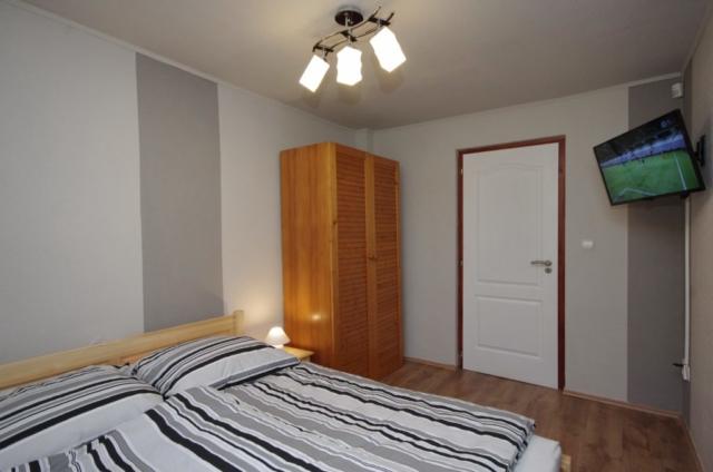 Téli szoba kétszemélyes ággyal, szekrénnyel és TV-vel a gyulai Bodza apartmanban