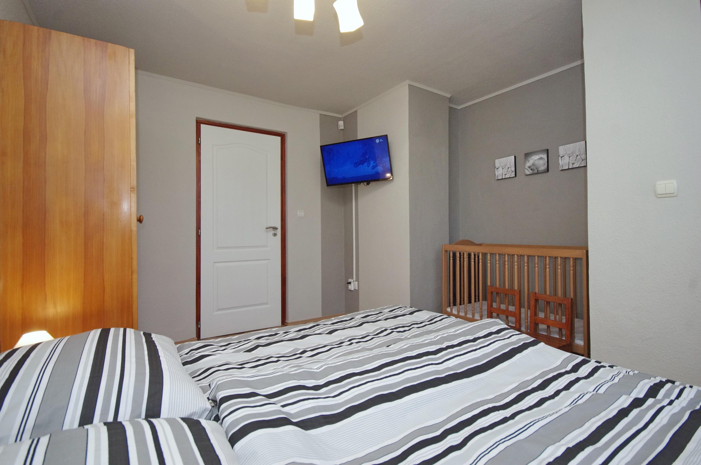 Babaágy és LED TV a téli szobában a gyulai Bodza apartmanban
